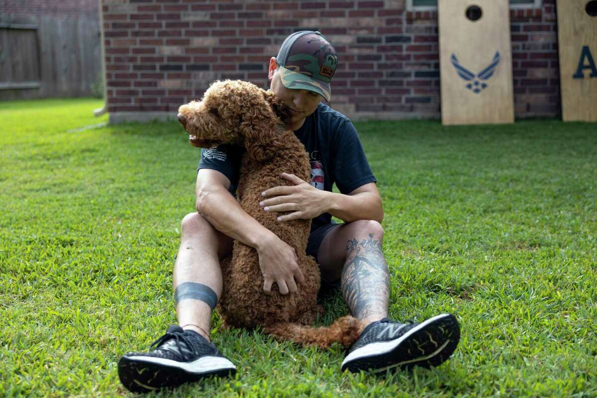 Montgomery County Sheriff's detective, Will Rollins hugs his dog, Andy the Australian Labradoodle, Wednesday, May 13, 2020.
