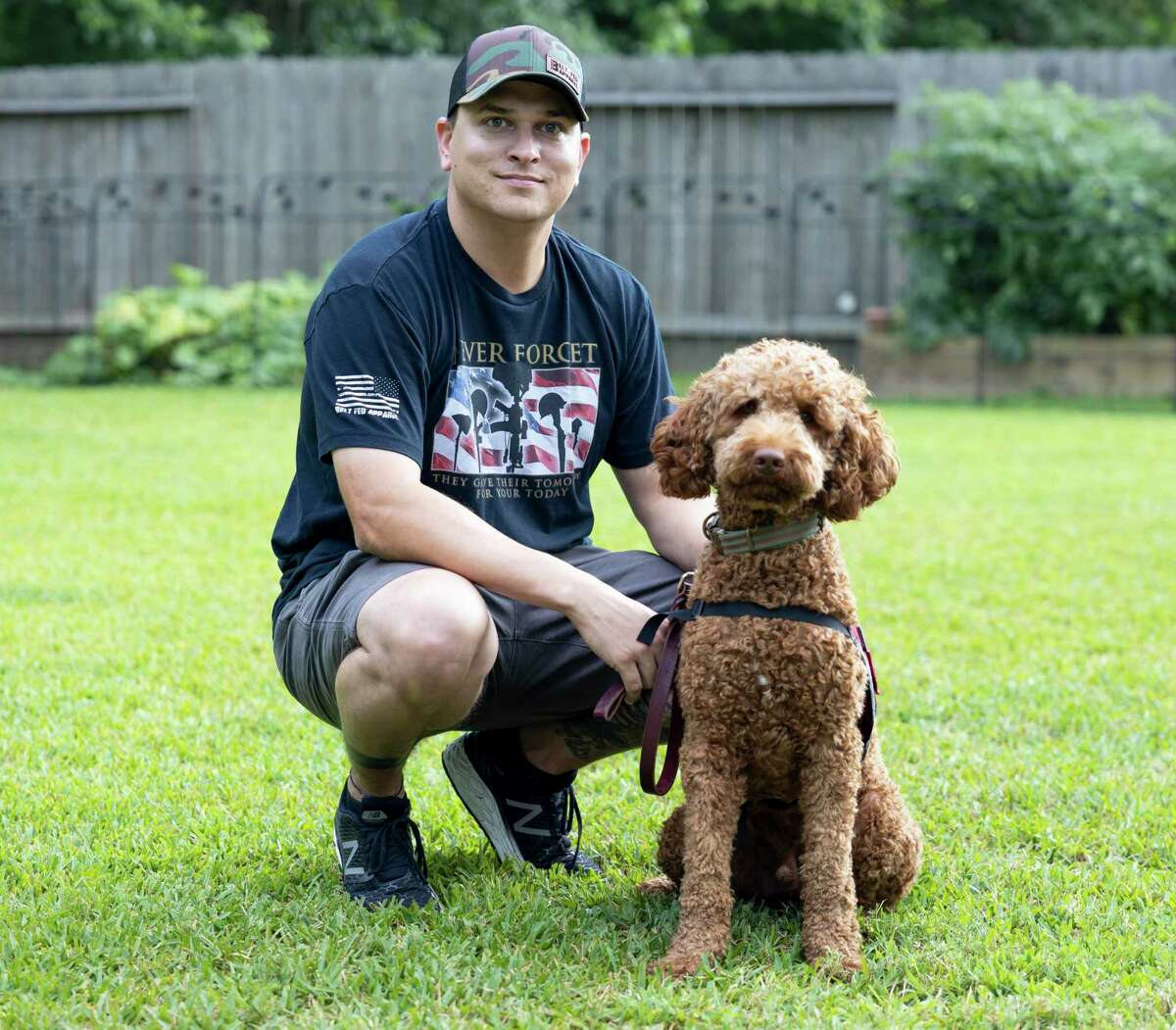 Montgomery County Sheriff's detective, Will Rollins, and Andy the Australian Labradoodle poses for a portrait in Conroe, Wednesday, May 13, 2020.