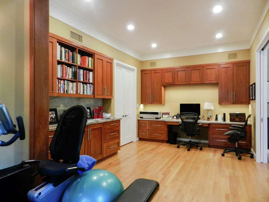 This inspirational home office includes custom cabinets and an exercise area.