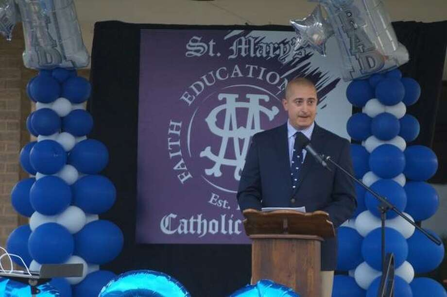 Principal Alex Pulido addresses the 22 eighth grade graduates at St. Mary's School in Alton on Monday. The outdoor ceremony practiced social distancing.