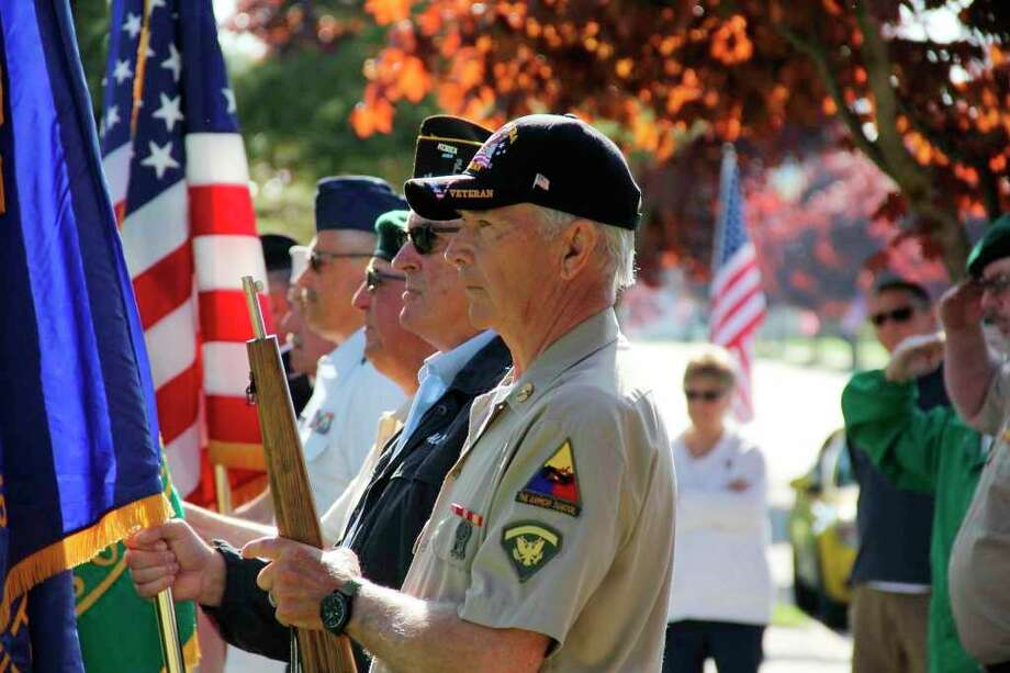 A local veteran holds a flag during a Memorial Day service in Ubly last year. Most of the local Memorial Day events have been canceled this year due to the coronavirus. (Tribune File Photo)