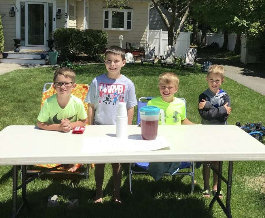 The Gulf Street quartet of Holden Orr, age 8, Lucas Dalby, age 10, Talyn Haley, age 6, and Andersen Orr, age 6, took advantage of the lifting of outside dining on Thursday to serve up ice tea to customers. Photo: Bill Bloxsom / Hearst Connecticut Media / Milford Mirror