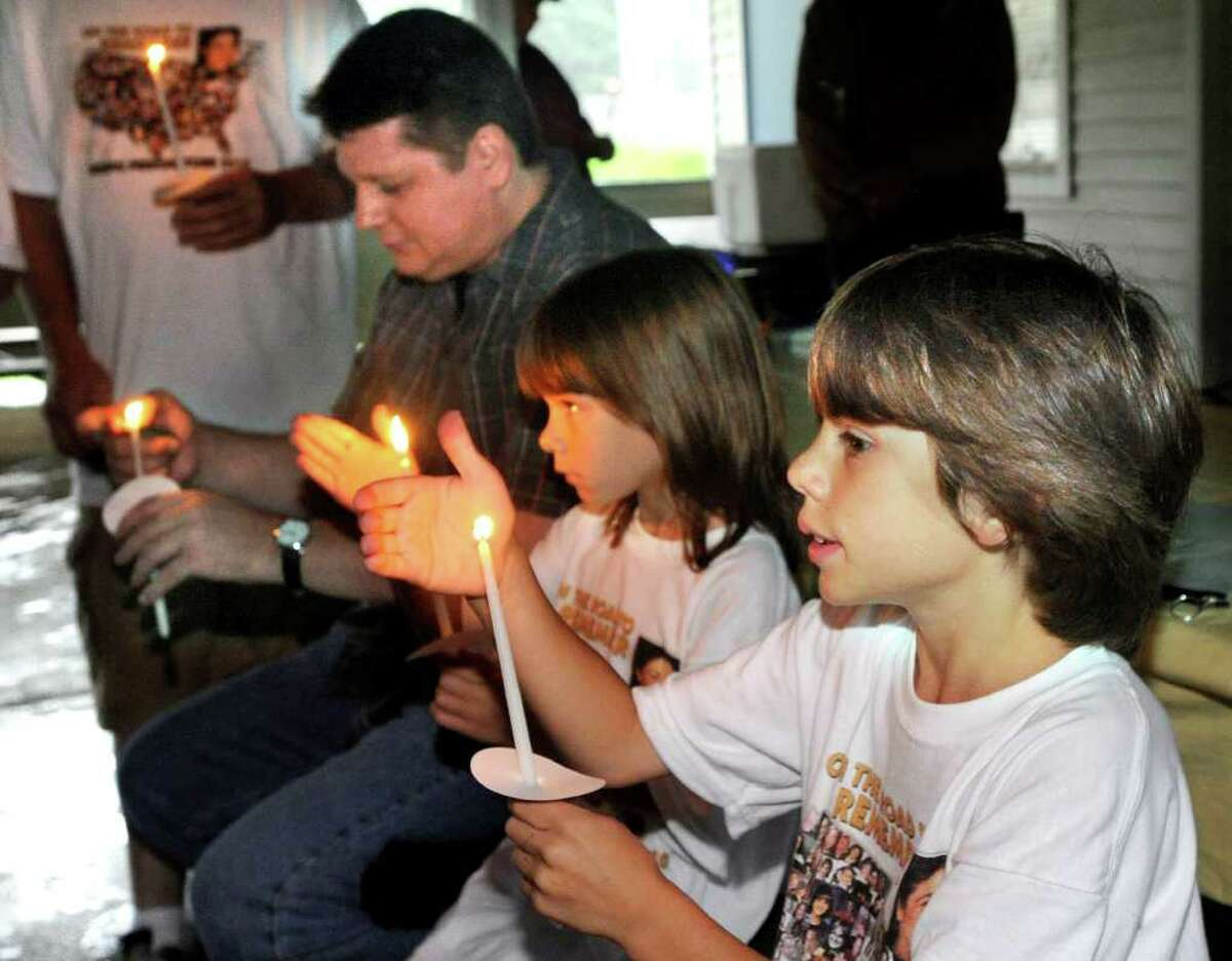 Lighting candles in memory of Mary Badaracco and others that are missing, are, from left, David Botsford, Emily and Aaron Valentino. Botsford's mother, Carmela Gutierrez, formerly of Brookfield, has been missing, since 1989. Photo taken Sunday, August 22, 100.