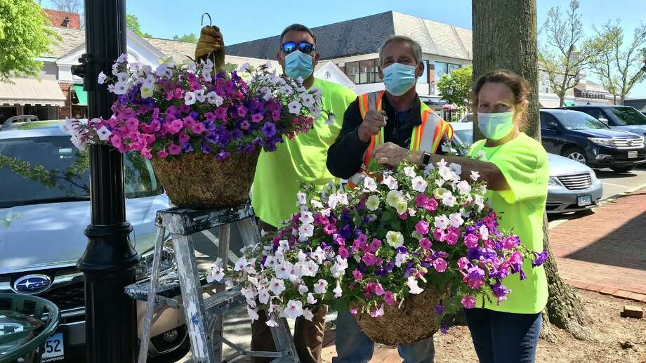 The New Canaan Department of Public Works is hard at work putting up the New Canaan Beautification League's hanging baskets around the town on Thursday, May 21. A total of 220 baskets went up this year, (2020), with 200 baskets of petunias for sunny areas, and 20 baskets with shade plants. The Beautification League has been providing the baskets for the town since 2009. They originally started with just over 100 baskets. The baskets were made possible thanks to the generous donations to the Beautification League's Annual Appeal. For more information about the Beautification League, or to become a member, visit newcanaanbeautification.org. Pictured left to right are: Louie Boice, Walk Jaykus, and Bianca Romano. Photo: Robin Bates-Mason / Contributed Photo