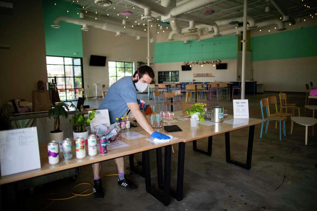 Urban South Brewery - HTX production assistant JJ Baker cleans up a table wearing a mask during the COVID-19 outbreak on Wednesday, May 20, 2020, in Houston.