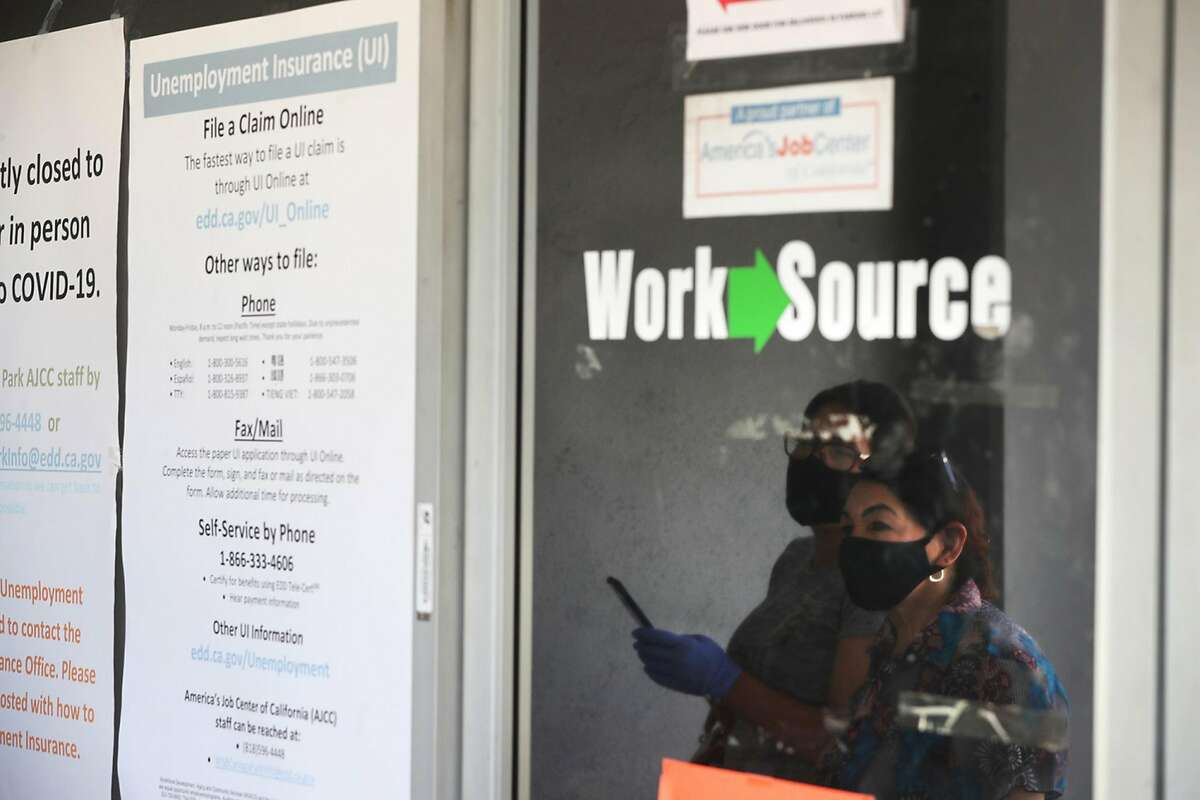 Estella Flores, right, and Maria Mora, left, are reflected in a window as they look for information in front of the closed California State Employment Development Department in Canoga Park in May.