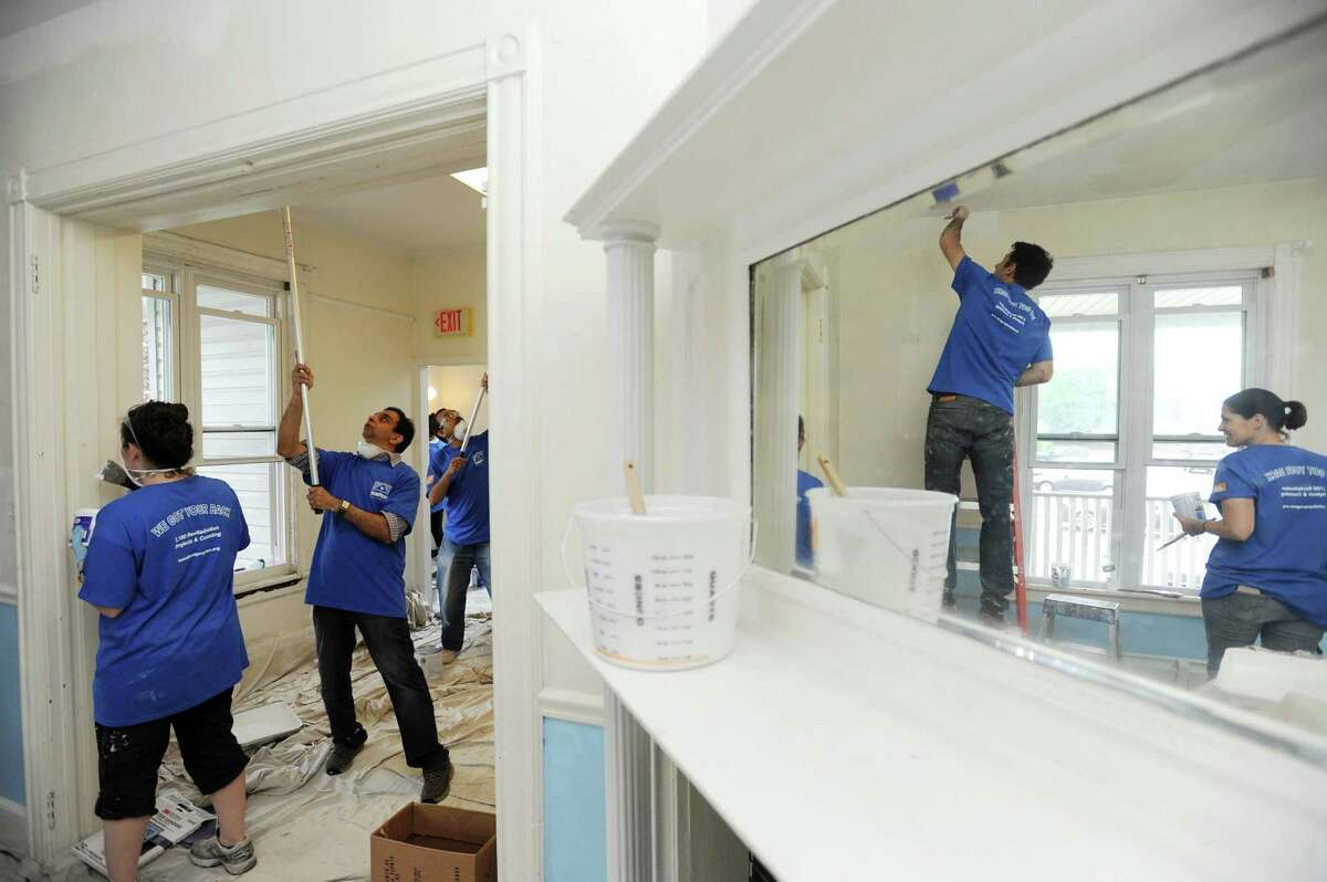 Volunteers from Stamford-based marketing company Synapse Group, Inc. work together to paint rooms inside Domus House on Washington Blvd. in Stamford, Conn. on Thursday, May 17, 2018.