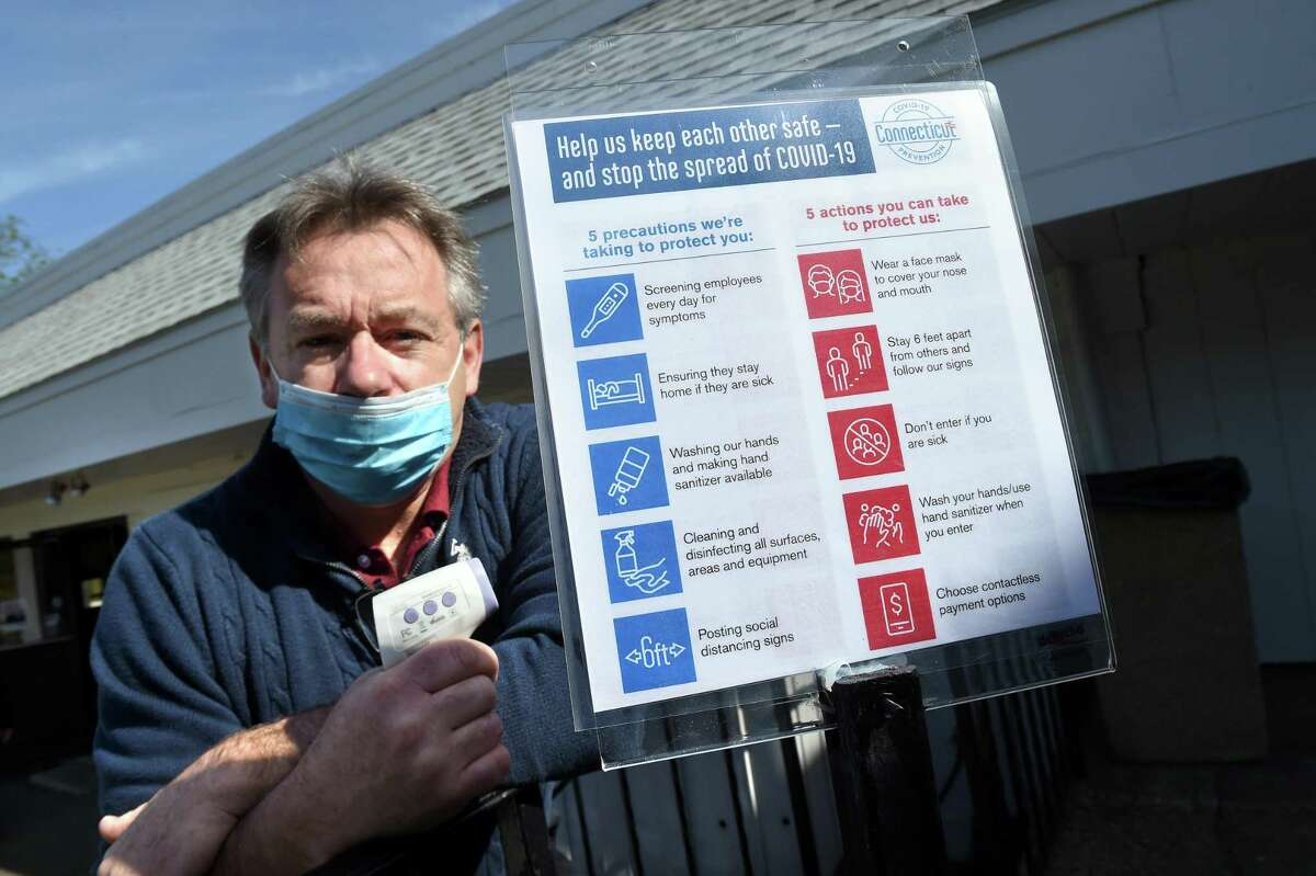 Tim Dillman, general manager at the Grassy Hill Country Club in Orange, is photographed at an outdoor patio where golfers can eat with a digital thermometer he uses to check employees at the start of their shifts on May 20, 2020. At right is a list of precautions for employees and customers for businesses to display.