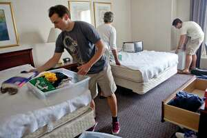 At left Benjamin North, 20, of Woodbury, a senior who will soon graduate, unpacks his clothes onto his bed at Nathan Hale Inn on the campus of the University of Connecticut Friday, August 24, 2012.