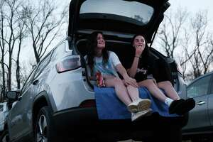 Teens enjoy some snacks from the back of a car. (Photo by Spencer Platt/Getty Images)