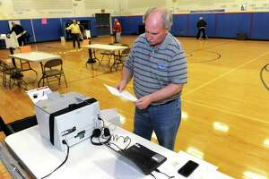 A file photo showing Stratford Registrar Rick Marcone testing a new voting station for handicapped voters as he and others prepare the gymnasium at Second Hill Lane Elementary School for Election Day voting in Stratford, Conn. Nov. 7, 2016.