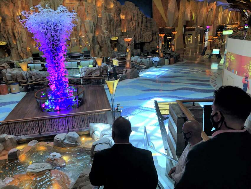 Officials lead media down the elevator in a nearly deserted Mohegan Sun Thursday.
