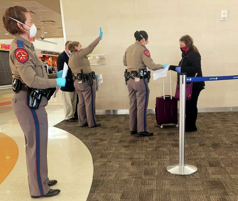 A team of Texas State Troopers greeted passengers leaving a United flight from Chicago at San Antonio International Airport. Travelers were required to fill out a quarantine form disclosing where they will shelter in place for the next 14 days. An executive order by Gov. Greg Abbott required travelers boarding planes in Chicago and other designations to quarantine once they arrive in Texas. Photo: Randy Diamond, Staff Photographer