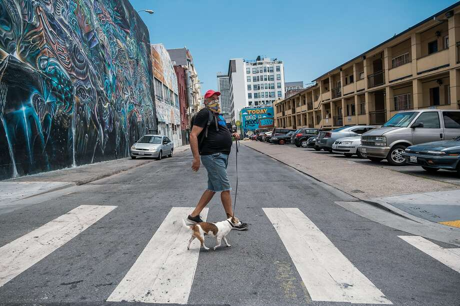 CJ Peoples walks his dog, Mister, through the Tenderloin. Peoples says that with the Curry Senior Center closed, he has less of a social life. Photo: Nick Otto / Special To The Chronicle
