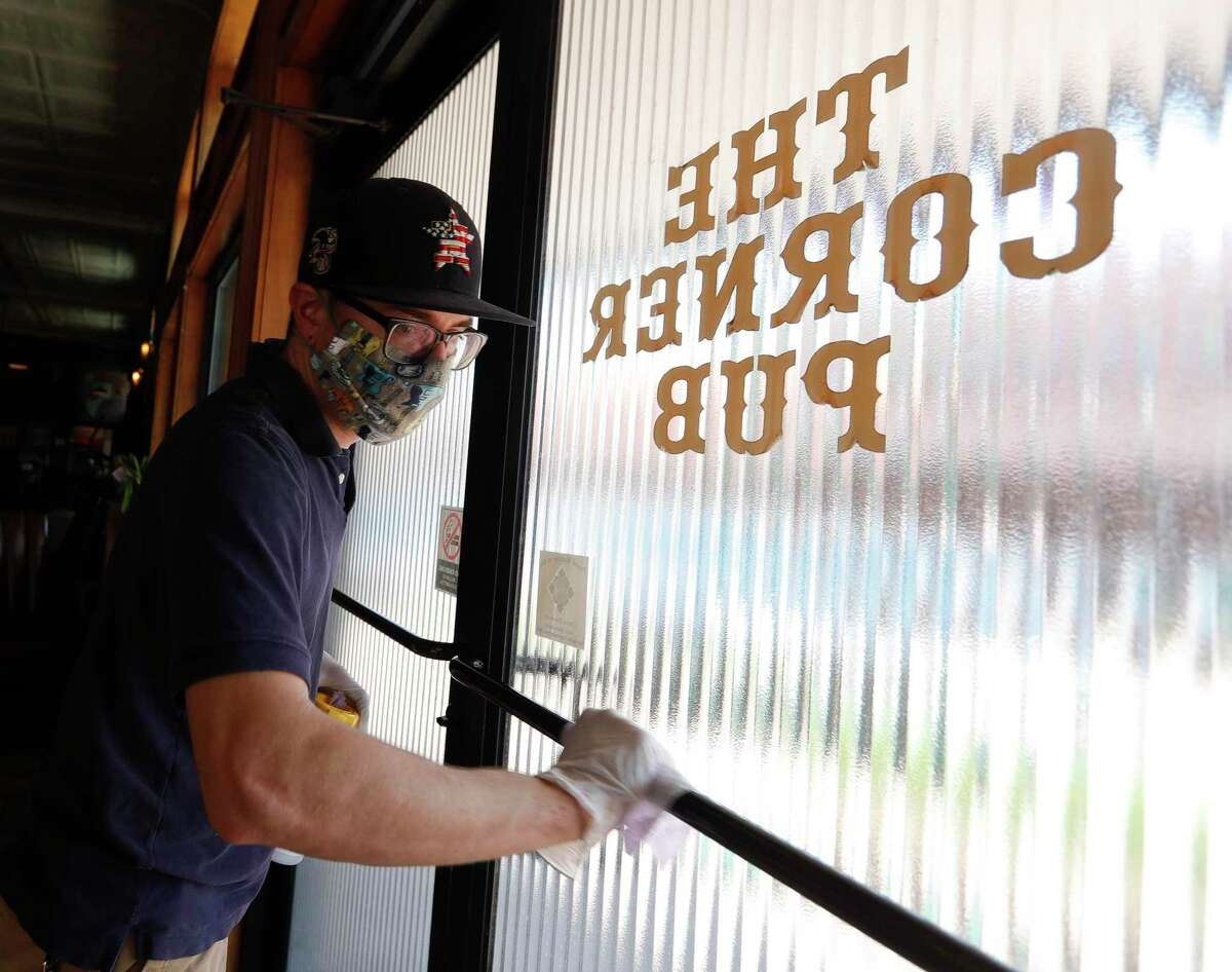 Kitchen Manager Trey Dryden disinfects door handles at The Corner Pub, Wednesday, April 20, 2020, in Conroe. The bar reopens to customers Friday with social distancing and other guidelines under Gov. Greg Abbott's phased reopening of the economy.