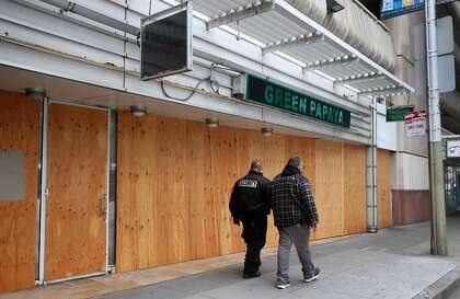 Plywood boards cover the windows at Green Papaya restaurant in San Francisco, which relied on foot traffic from the Moscone Center before shelter-in-place began.
