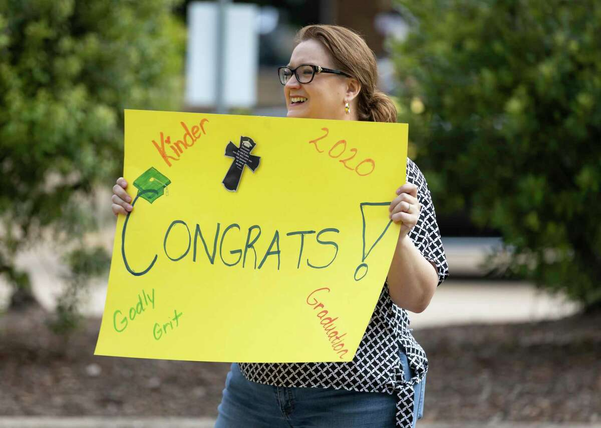A woman holds a sign congratulating students graduating from kindergarten at The Woodlands Christian Academy, Thursday, May 21, 2020. Around 40 students participated in the drive-by graduation ceremony where they received gifts from teachers and staff at the academy.