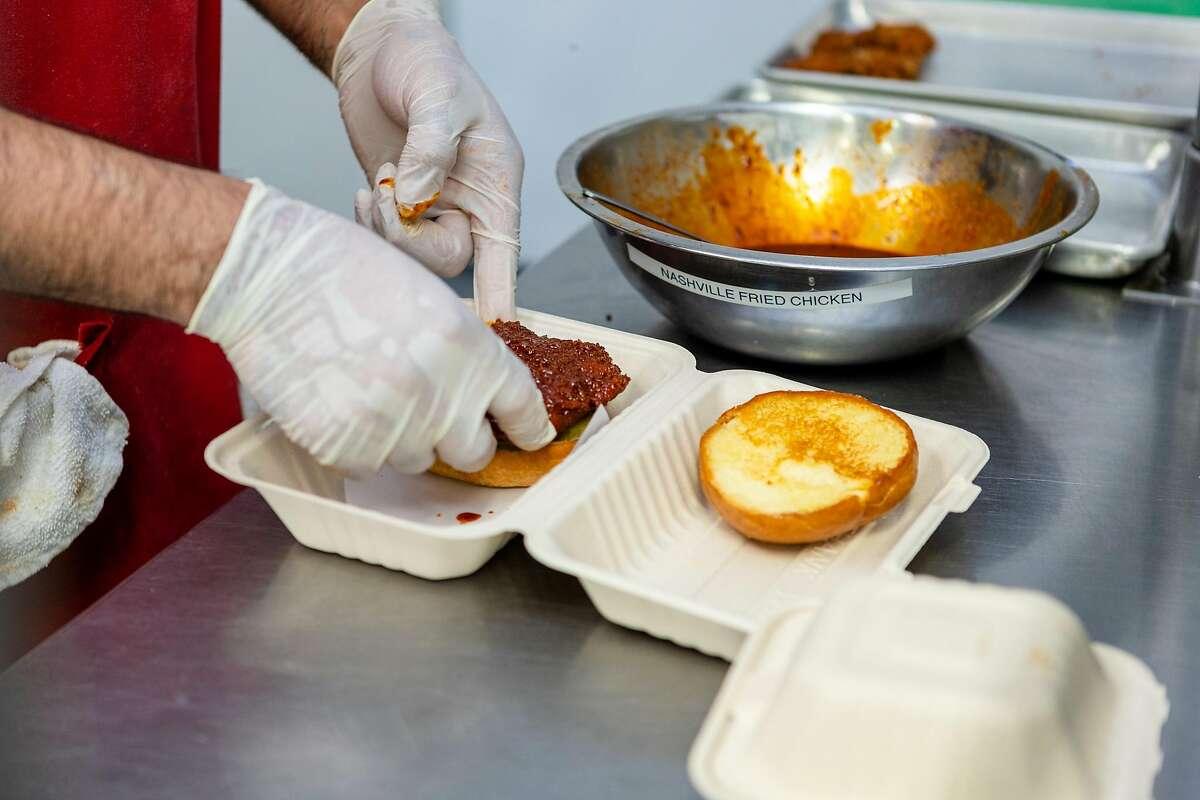 Eduardo Soto, kitchen manager, prepares a �Nashville Hot Chicken Sandwich� at Chicken as Cluck�s kitchen on Wednesday, May 20, 2020, in San Francisco, Calif.