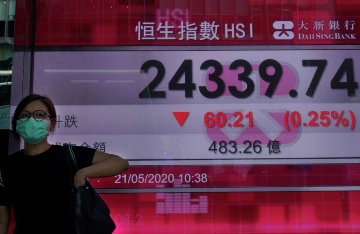A woman wearing a face mask walks past a bank's electronic board showing the Hong Kong share index at Hong Kong Stock Exchange Thursday, May 21, 2020. Asian stock markets are mixed after Wall Street rose amid Chinese trade tension with Washington and Australia. Investors looked ahead to Fridaya€™s meeting of Chinaa€™s legislature for details of possible new steps by Beijing to stimulate its virus-battered economy.(AP Photo/Vincent Yu)