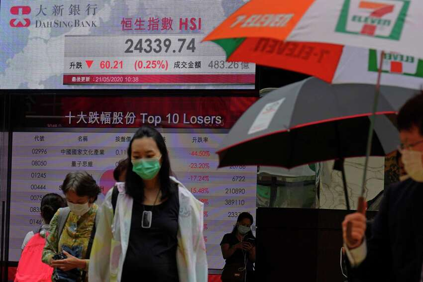 People wearing face masks walk past a bank's electronic board showing the Hong Kong share index at Hong Kong Stock Exchange Thursday, May 21, 2020. Asian stock markets are mixed after Wall Street rose amid Chinese trade tension with Washington and Australia. Investors looked ahead to Fridaya€™s meeting of Chinaa€™s legislature for details of possible new steps by Beijing to stimulate its virus-battered economy.(AP Photo/Vincent Yu)