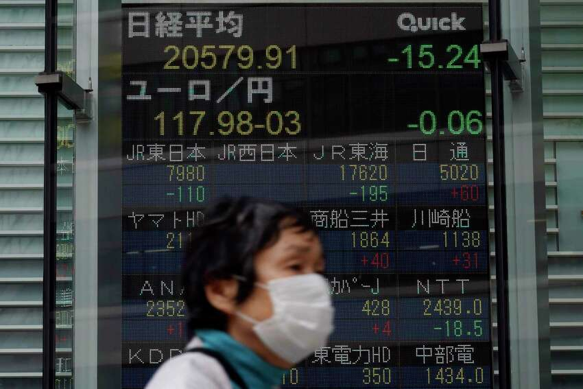 A masked woman walks past an electronic stock board showing Japan's Nikkei 225 index at a securities firm in Tokyo Thursday, May 21, 2020. Asian stock markets are mixed after Wall Street rose amid Chinese trade tension with Washington and Australia. Investors looked ahead to Fridaya€™s meeting of Chinaa€™s legislature for details of possible new steps by Beijing to stimulate its virus-battered economy. (AP Photo/Eugene Hoshiko)