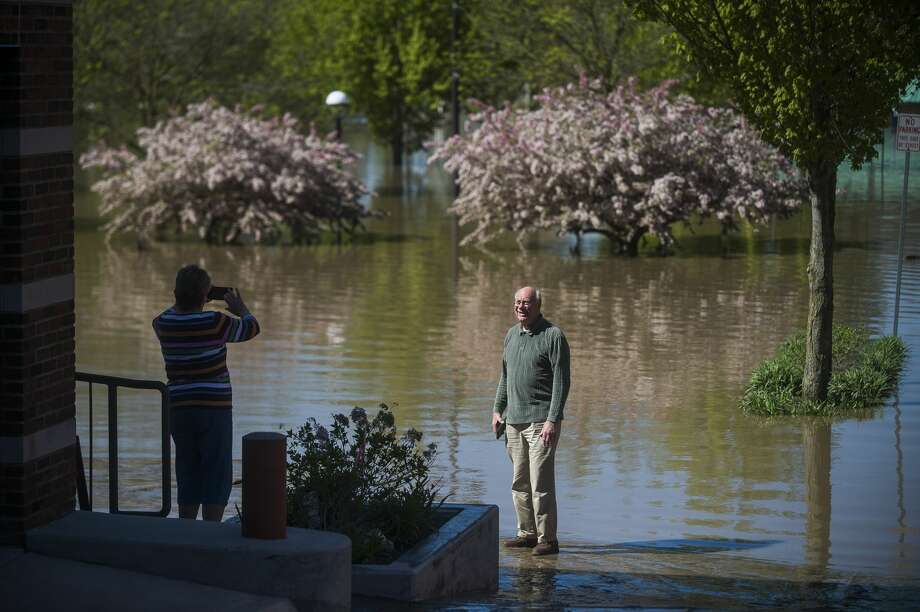 A man poses for a photo near floodwater in downtown Midland Thursday morning. (Katy Kildee/kkildee@mdn.net) Photo: (Katy Kildee/kkildee@mdn.net)