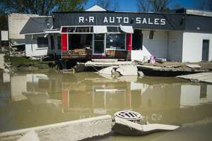 Floodwater surrounds R&R Auto Sales in downtown Sanford Thursday afternoon. (Katy Kildee/kkildee@mdn.net)