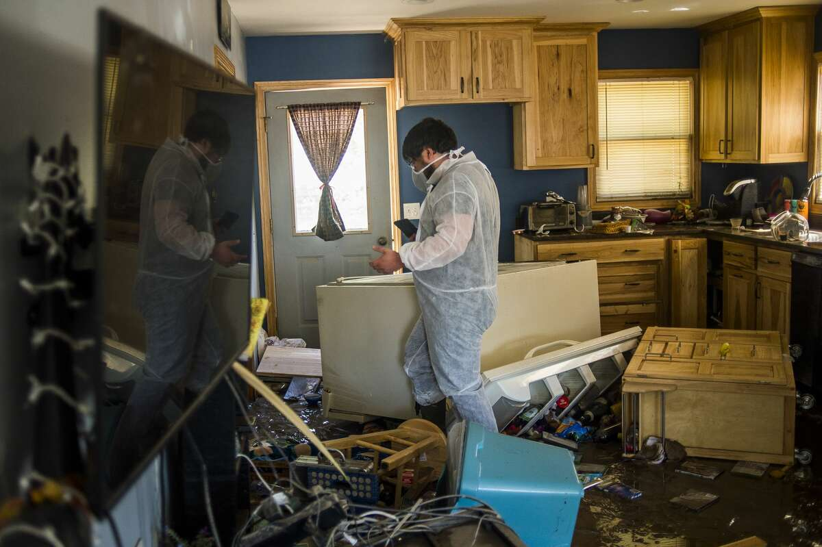 Thomas Perrin walks through his kitchen while surveying the flood damage in his home Thursday afternoon in downtown Sanford. (Katy Kildee/kkildee@mdn.net)