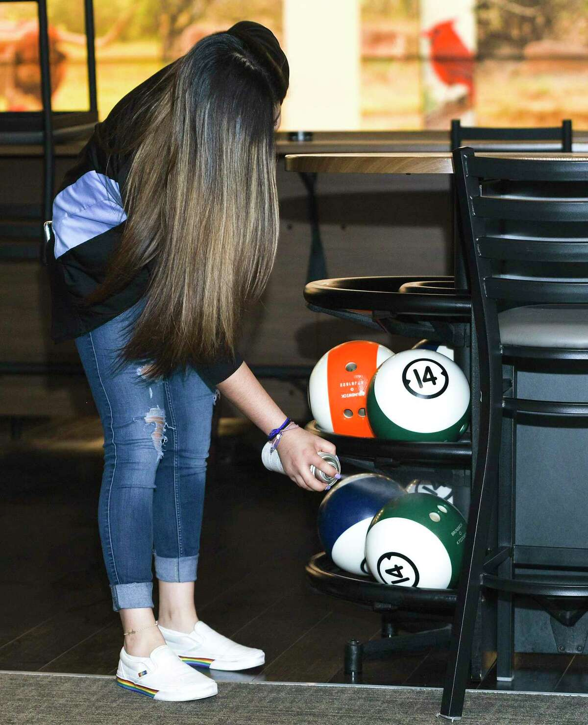 Pla-Mor employee Karla Rivas disinfects bowling balls prior to the entertainment center's soft opening, Thursday, May 21, 2020. Pla-Mor is set to follow social distancing guidelines as it officially open, with restrictions, on Friday.
