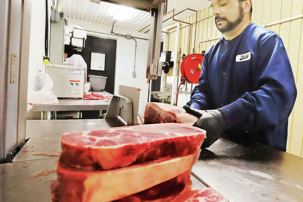 "Hansen Meats butcher Bud Ramsay cuts up pork steaks at the Alton store this week. Third-generation owner Ryan Hansen said he's seen a dramatic surge in demand at his stores and his staff is ""stretched to capacity."""