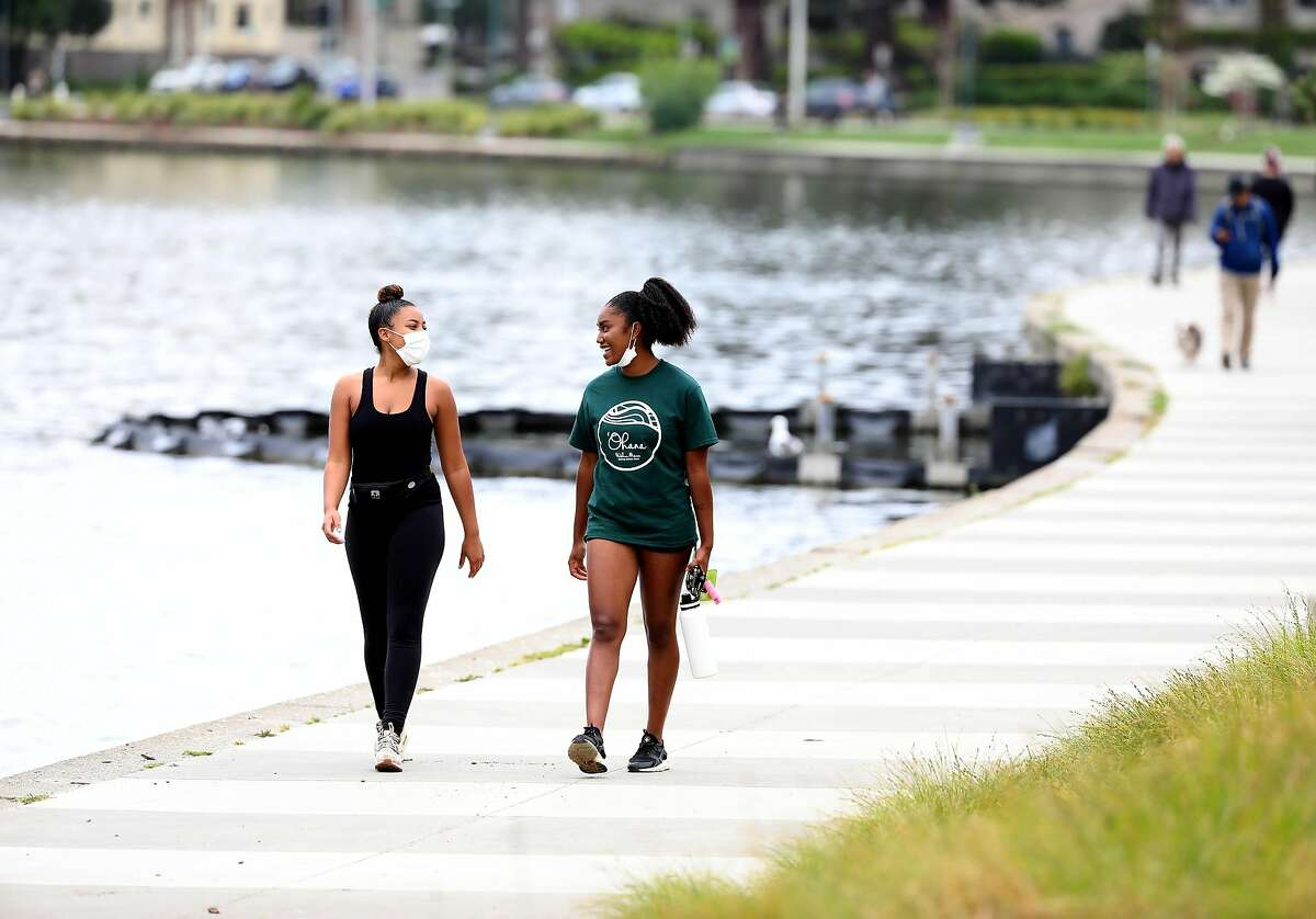Maite Wallace, left, and Farah Norwood, both of Oakland, converse during their morning walk at Lake Merritt on Friday, April 17, 2020, in Oakland, Calif. Bay Area counties are expected to announce a new order requiring residents to wear masks/facial coverings beginning at noon next Wednesday. The move accompanies an expected move to relax elements of the stay at home orders starting in early May.
