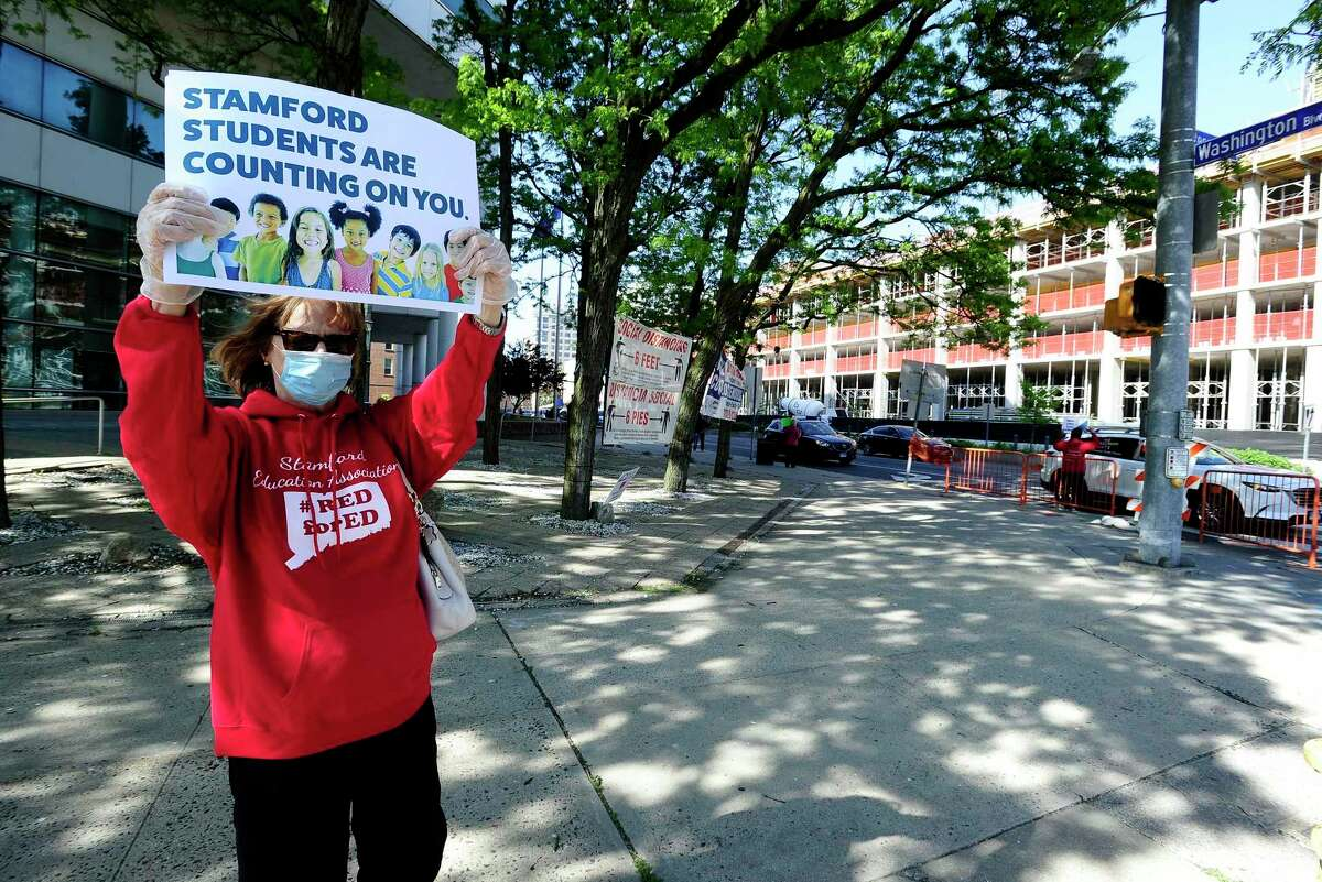 Diane Phanos, president of Stamford teachers union, holds a sign in front of the Stamford Government Center on May 21, 2020, urging city officials to fund Stamford schools.