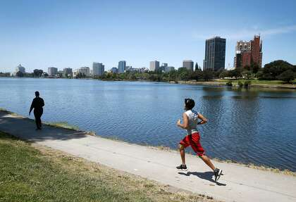 People walk and run around Lake Merritt in Oakland this month. Lake Merritt has been a popular destination during the coronavirus pandemic despite shelter-in-place orders.