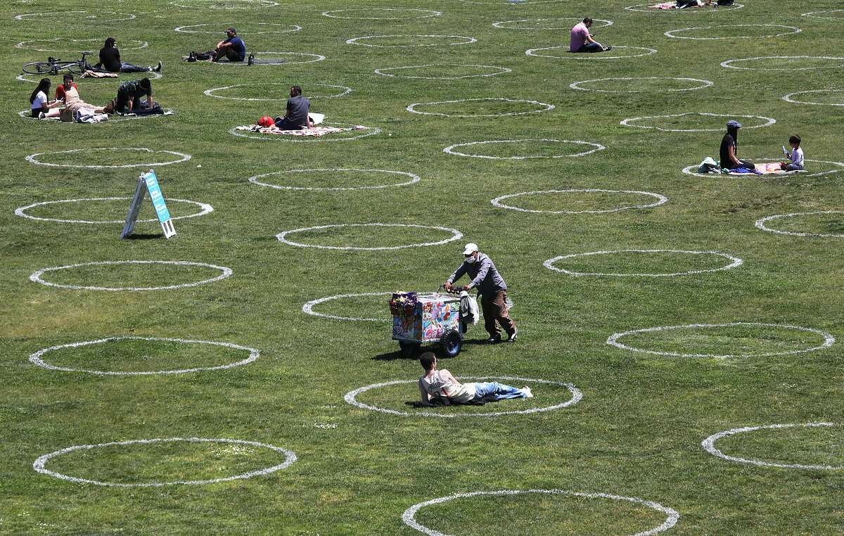 """�Human parking spots"""" are marked at Mission Dolores Park seen during lunch time on Thursday, May 21, 2020, in San Francisco, Calif. San Francisco Recreation & Parks Department painted social-distance guidance circles on the parks lawn."""