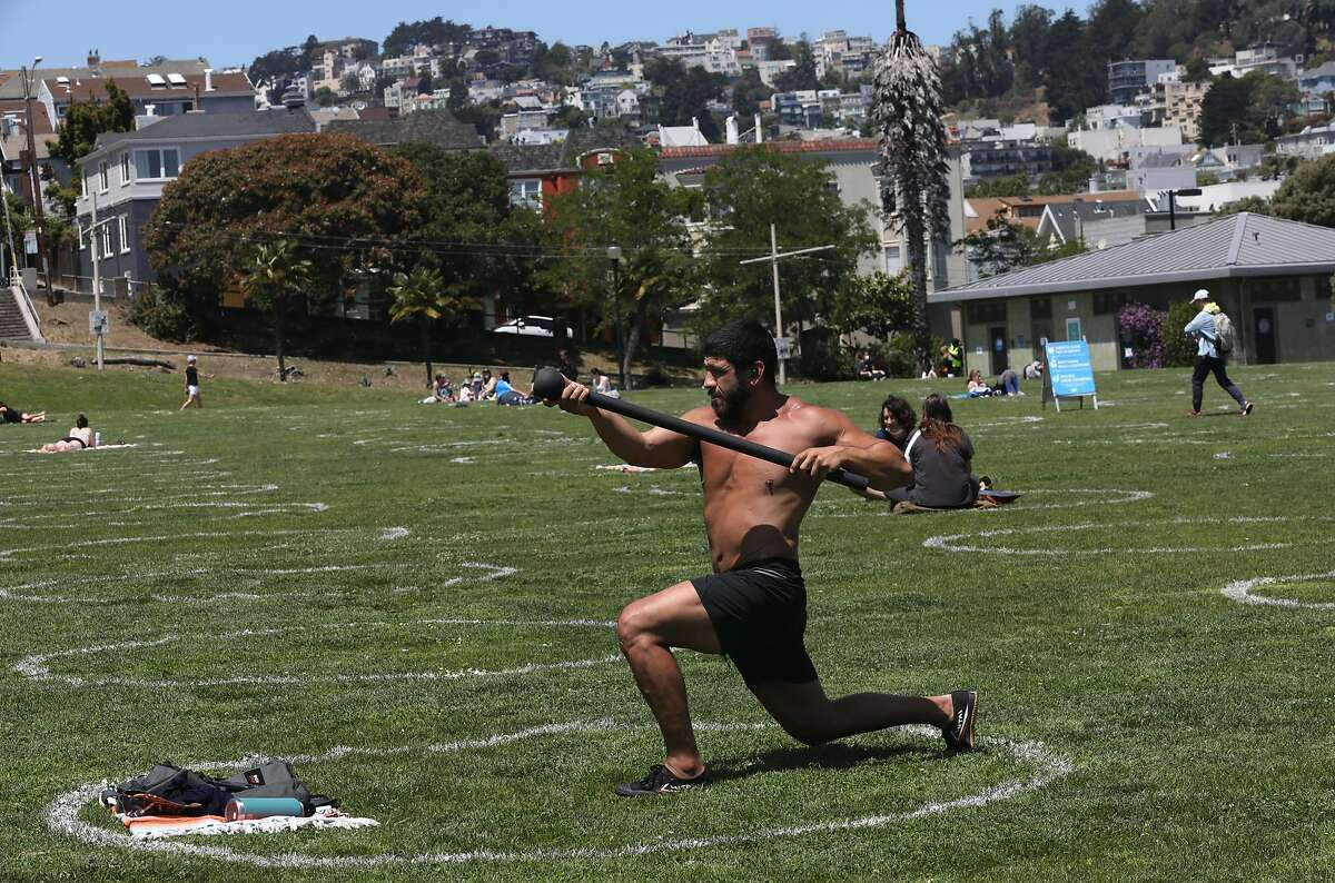 Nate Juarez exercises with a steel mace in a painted circle at Mission Dolores Park seen during lunch time on Thursday, May 21, 2020, in San Francisco, Calif. San Francisco Recreation & Parks Department painted social-distance guidance circles on the parks lawn.