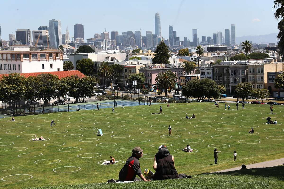 """""""Human parking spots"""" are marked at Mission Dolores Park seen during lunch time on Thursday, May 21, 2020, in San Francisco, Calif. San Francisco Recreation & Parks Department painted social-distance guidance circles on the parks lawn yesterday."""