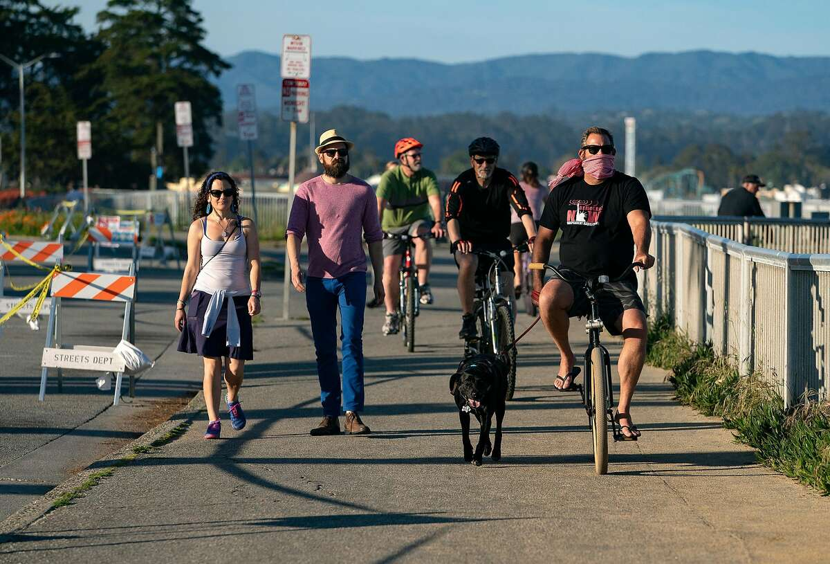 People hike and bike along W Cliff Dr. on Wednesday, April 22, 2020 in Santa Cruz, Calif.