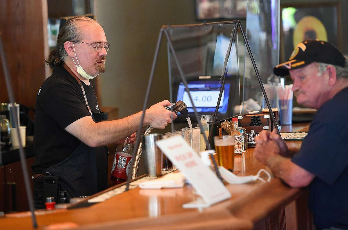 A bartender makes drinks for a customer on the other side of a protective barrier at Downtown Joe's restaurant and bar in Napa, California on May 20, 2020. Taking advantage of Napa's liberalized shelter-in-place rules, some restaurants have begun to fully reopen with new safety requirements in place.
