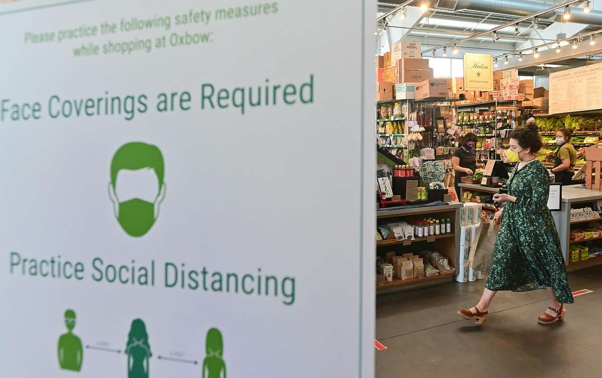 A shopper walks through Oxbow Market in Napa, California on May 20, 2020. Taking advantage of Napa's liberalized shelter-in-place rules, some restaurants have begun to fully reopen with new safety requirements in place.