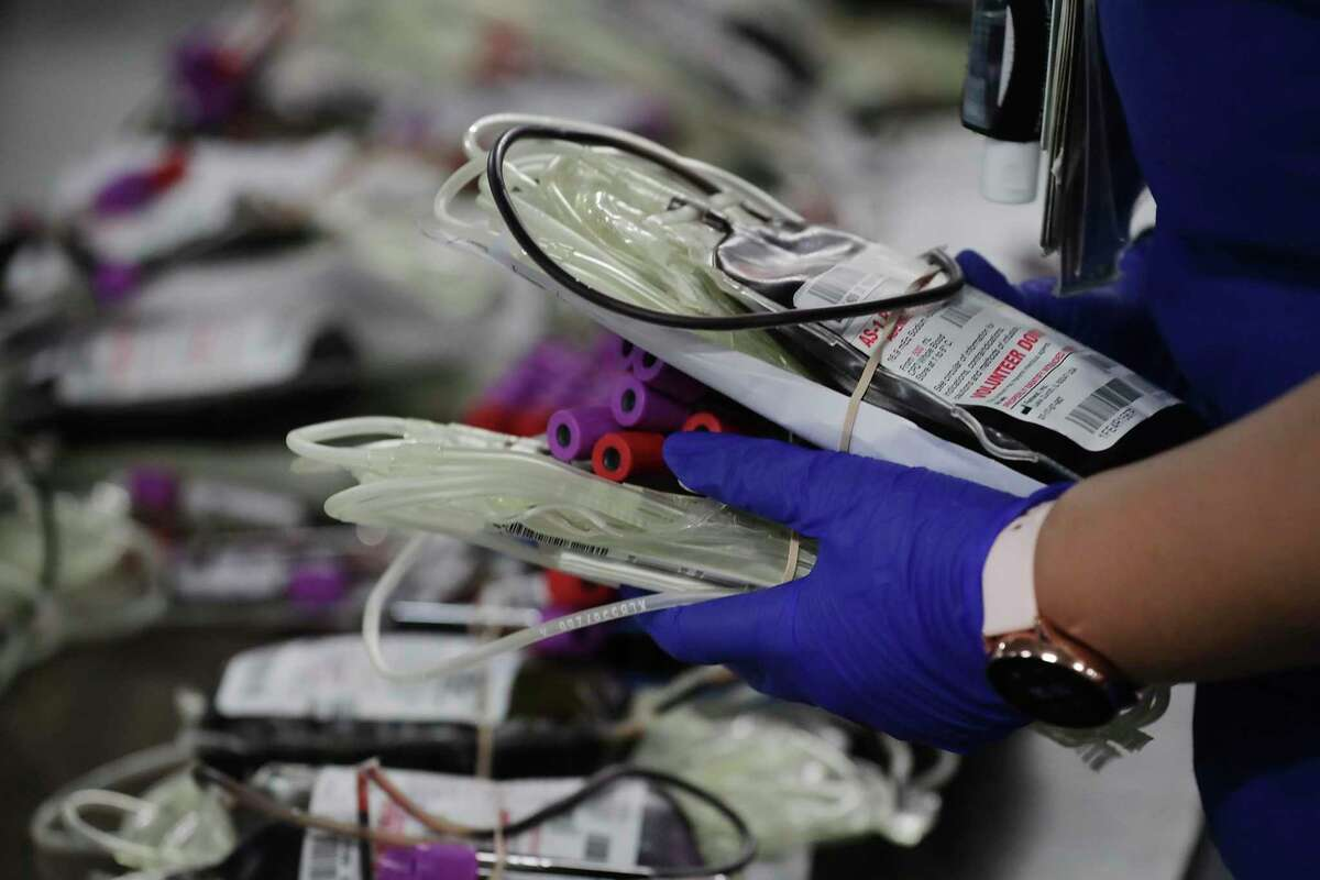 A phlebotomist collects units of blood donated at a South Texas Blood and Tissue Center blood drive at the Alamodome last month. The center is asking survivors of COVID-19 to donate plasma to help others recover faster and ease the strain on hospitals. Cases are surging and the plasma is in short supply.