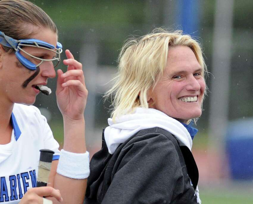 At right, Darien High School girls lacrosse caoch Lisa Lindley smiles during the CIAC state playoff girls lacrosse match between Darien High School and South Windsor High School at Darien, Conn., Tuesday, June 2, 2015.