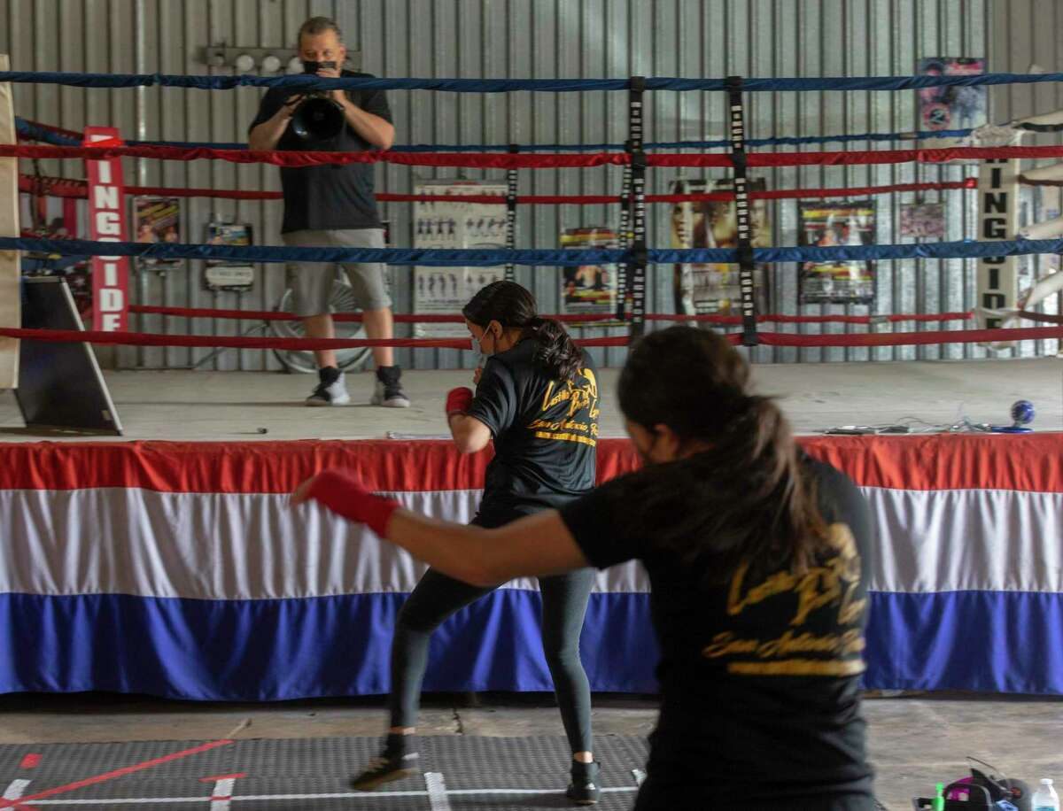Wendy, front, and Odet Mota, middle, exercise Thursday, May 21, 2020, at Castillo's Boxing Gym on Pleasanton Road as coach Gilbert Garza watches from the ring. Gyms are slowly starting to open as Texas has reduced COVID-19 coronavirus restrictions.