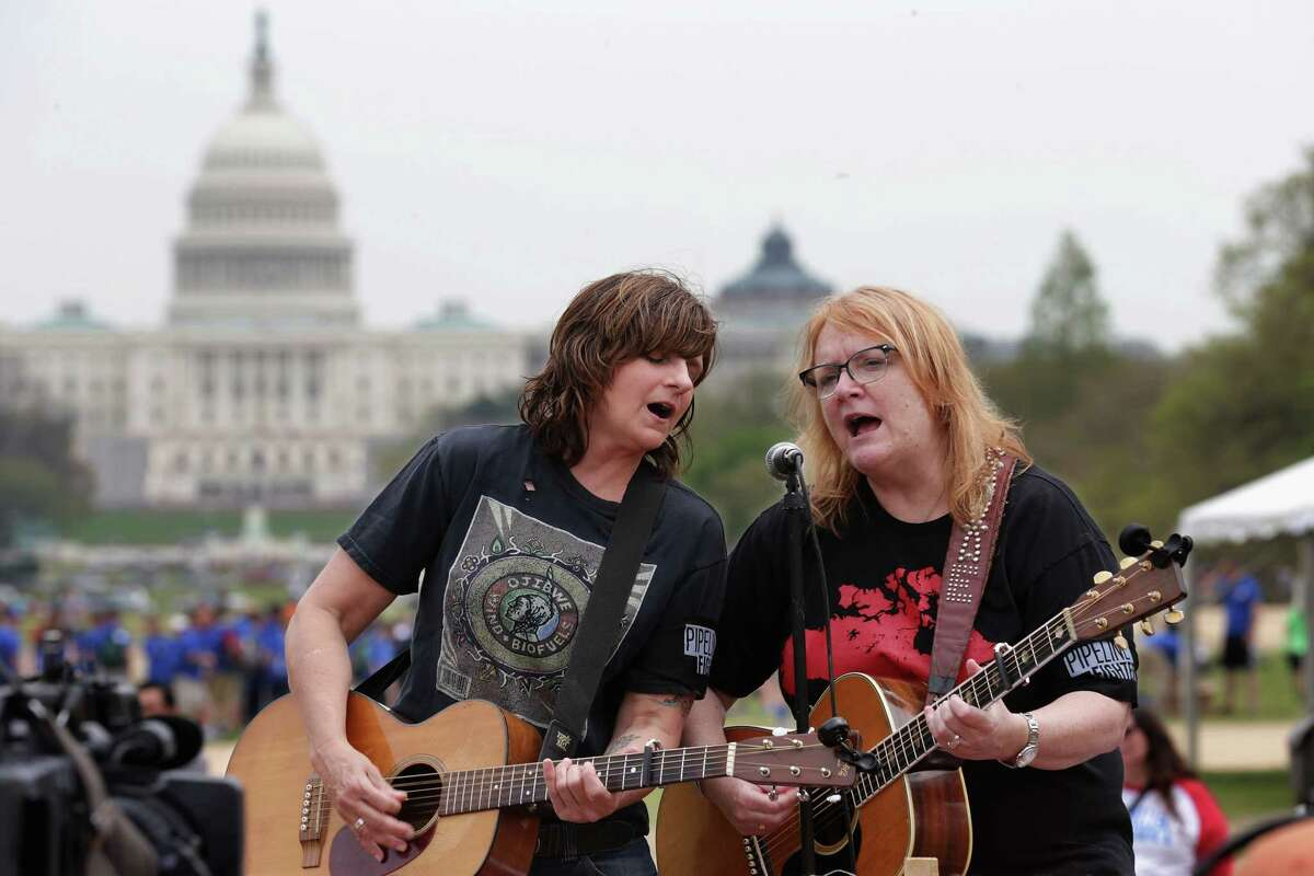 """WASHINGTON, DC - APRIL 22: Amy Ray (L) and Emily Saliers of The Indigo Girls perform during a demonstration against the proposed Keystone XL pipeline on the National Mall April 22, 2014 in Washington, DC. As part of its """"Reject and Protect"""" protest, the Cowboy and Indian Alliance is organizing a weeklong series of actions by farmers, ranchers and tribes to show their opposition to the pipeline. (Photo by Chip Somodevilla/Getty Images)"""