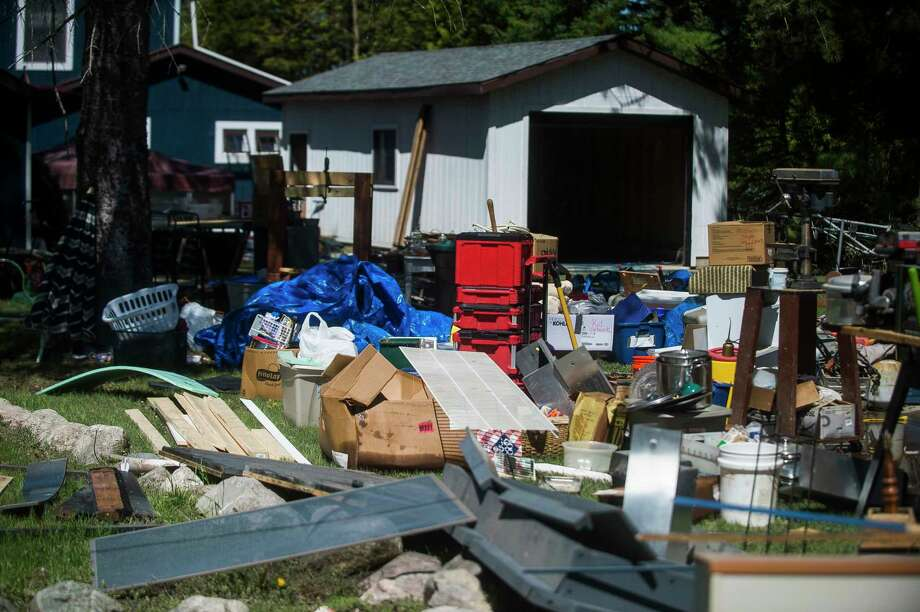 Belongings lie on the lawn of a resident along the east shore of Wixom Lake Thursday afternoon, offering assistance to families devastated by flooding. (Katy Kildee/kkildee@mdn.net)