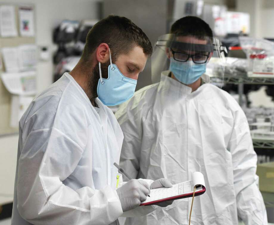 "Medical laboratory scientist Dyllon Reilly, left, and Sgt. Nick Spencer, who is part of the U.S. Army Urban Augmentation Medical Task Force, run coronavirus tests in the lab at Stamford Hospital in Stamford, Conn. Thursday, May 14, 2020. Stamford Hospital is using the Polymerase Chain Reaction (PCR) testing system, which multiplies a strand of potential virus RNA until millions of strains are present, at which point a ""read"" is performed. More than 9,000 of these COVID-19 tests have been performed at Stamford Hospital since March 4. Photo: Tyler Sizemore / Hearst Connecticut Media / Greenwich Time"