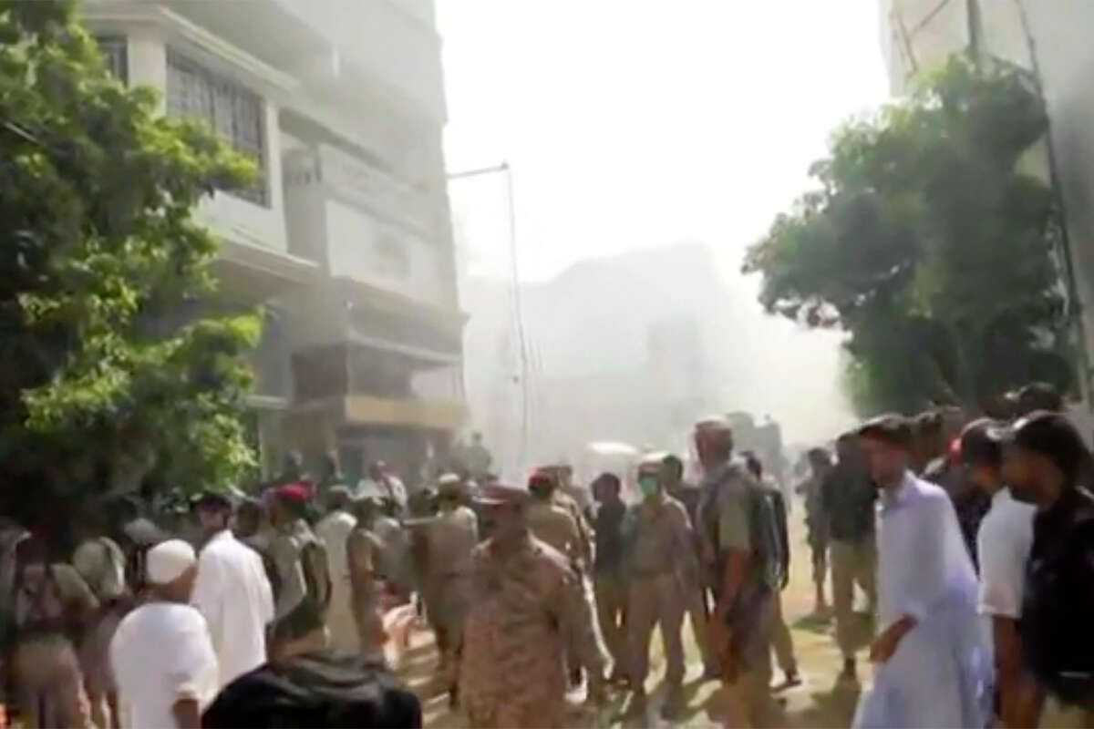 In this image made from video, crowds gather at scene of plane crash near Karachi, Friday, May 22, 2020. A passenger plane carrying more than one hundred passengers and crew belonging to state-run Pakistan International Airlines crashed near the southern port city of Karachi on Friday, a civil aviation official said.