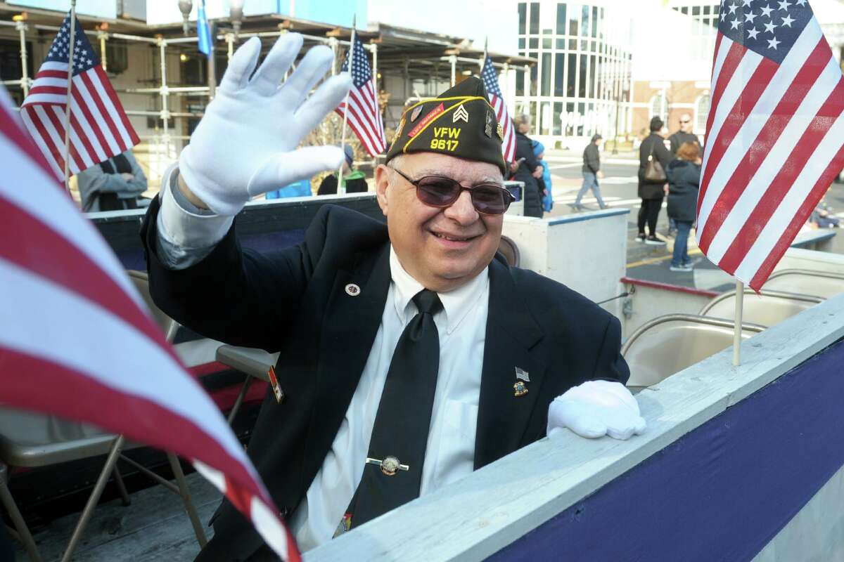 Tony Venezio, a US Army veteran from Stamford, waves to the crowd as he rides in the Veterans Day parade in downtown Stamford, Conn. Nov. 11, 2019.