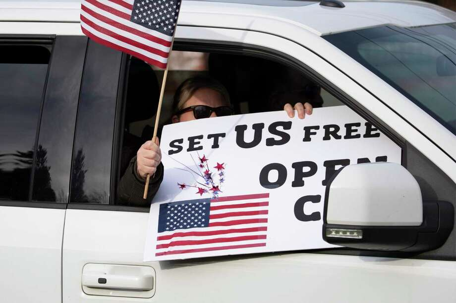 """A passenger in a car participates in a rally of honking vehicles that pass back and forth in front of the governor's mansion during the coronavirus pandemic, Monday, April 20, 2020 in Hartford, Conn. Her sign reads, """"Set Us Free."""" The rally, organized by CT Liberty Rally, is asking Gov. Ned Lamont to allow people to make their own decisions when it comes to their health. Photo: Mark Lennihan / Associated Press / Copyright 2020 The Associated Press. All rights reserved"""