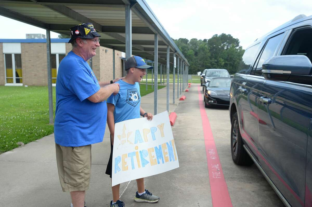George Jordan, who has taught 41 of his 42 years at Hardin - Jefferson talks with a parade of current and former students and fellow staff, including Jackson Lindow, at a drive-through retirement party outside Sour Lake Elementary, where he has taught science for over 20 years. Despite there being no STAAR tests this year, Jordan had a tent set up on the roof and planned to spend the night Thursday, per tradition the last 10-plus years when students met their their passing criteria. Jordan says,