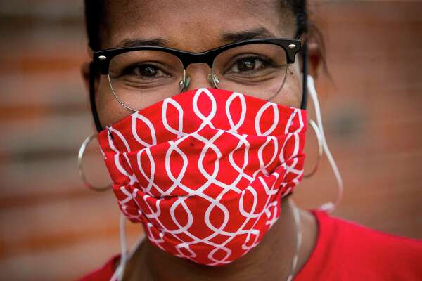 Valencia Lewis, of Communities In Schools, wears a mask during a student computer pick up arranged through a partnership between CIS and Comp-U-Dot at Hogg Middle School on Thursday, May 21, 2020 in Houston. Houston ISD and other schools across the region are working to get computers to all students for remote learning during the coronavirus shutdown. HISD is pledging to keep delivering computers to all students beyond the pandemic.